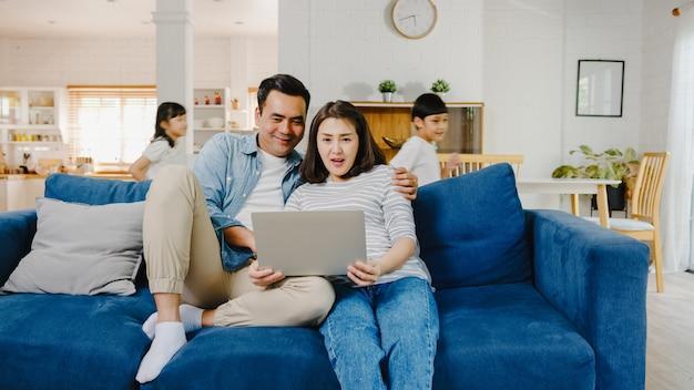 Il papà e la mamma della famiglia asiatica si siedono sul divano e si divertono a fare shopping online sul laptop mentre figlia e figlio si divertono a gridare correre intorno al divano nel soggiorno di casa