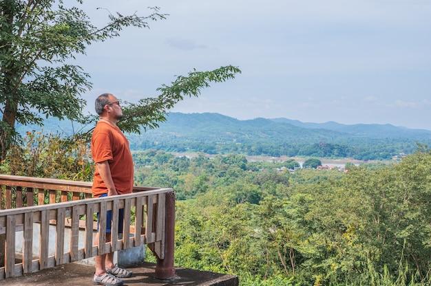 태국 푸 창 노이 치앙 칸 지구 로이 시의 풍경이 보이는 아시아 뚱뚱한 남자. 치앙 칸은 구시가지이며 태국 관광객에게 매우 인기 있는 목적지입니다.
