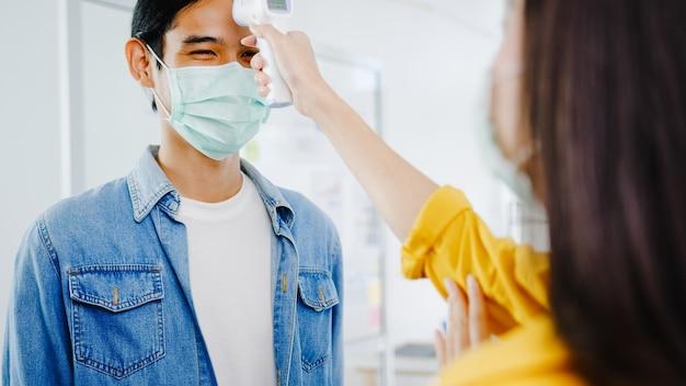 착용 보호 안면 마스크를 실시하는 아시아 여성 접수 원은 사무실에 들어가기 전에 고객의 이마에 적외선 온도계 검사기 또는 온도 건을 사용합니다. 코로나 바이러스 이후 생활 방식이 새로운 정상입니다.