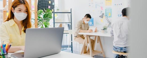 Le donne asiatiche indossano una maschera per il distacco sociale in una nuova situazione normale per la prevenzione dei virus durante l'utilizzo di laptop e separate da un supporto in acrilico in ufficio. vita e lavoro dopo il coronavirus.