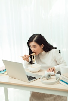 Asia freelance business woman eating instant noodles while working on laptop in living room at home office