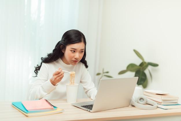 ホームオフィスのリビングルームでラップトップに取り組んでいる間インスタントラーメンを食べるアジアのフリーランスのビジネスウーマン