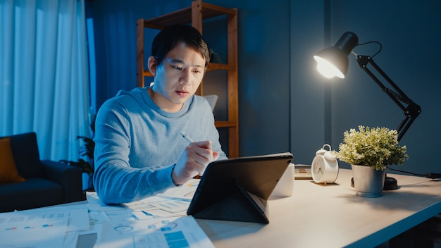 Азия внештатный бизнесмен фокус рабочая ручка писать на планшетном компьютере занят полным графиком документов на столе в гостиной