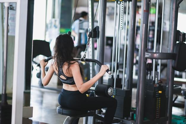 Asia girl doing exercises on the simulator