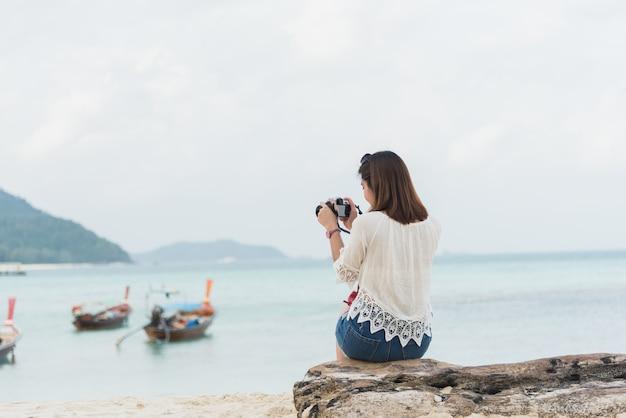 Азиатская девушка сидит и фотографирует на пляже