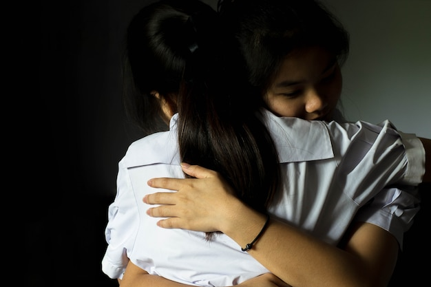Asia girl student embracing to comfort to her best friend.