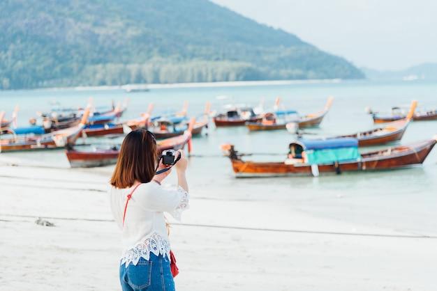 Девушка азии фотографирует на пляже