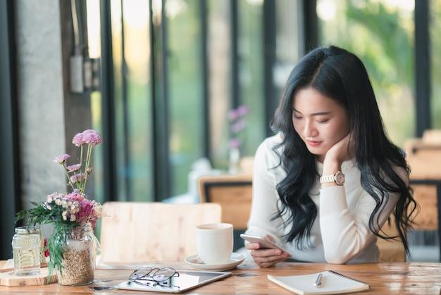 카페에서 휴대 전화를 사용 하여 아시아 소녀