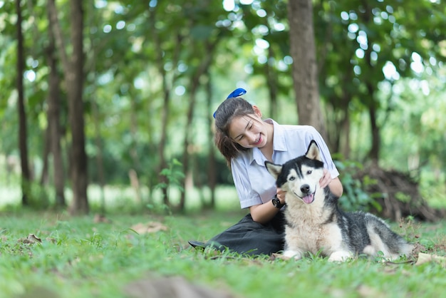 Asia girl wearing uniform playing with a siberian husky