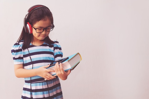 音楽を聴くと本を保持しているヘッドフォンでアジアの少女