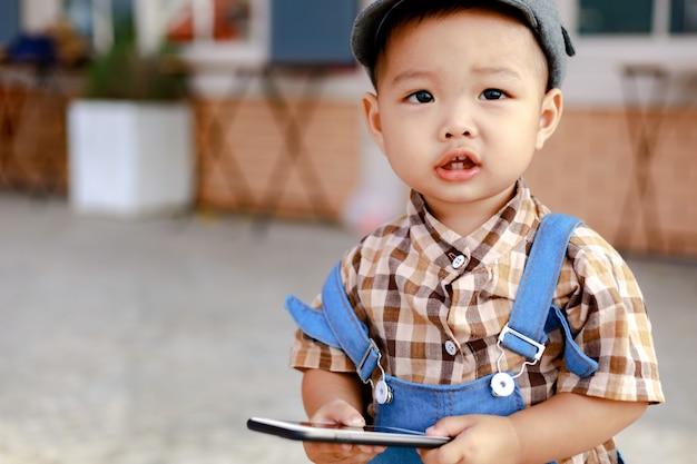 Азия ребенок держит и пытается играть в смартфон