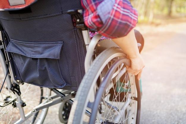 Азия леди женщина пациент на инвалидной коляске в парке.