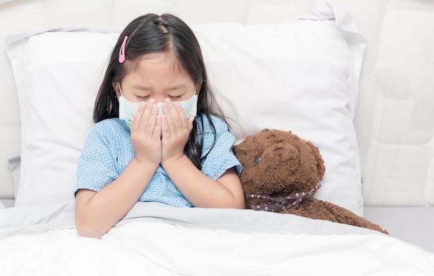 Азия маленькая девочка кашель и гигиеническая маска гигиены. вирусная защита и концепция здравоохранения.