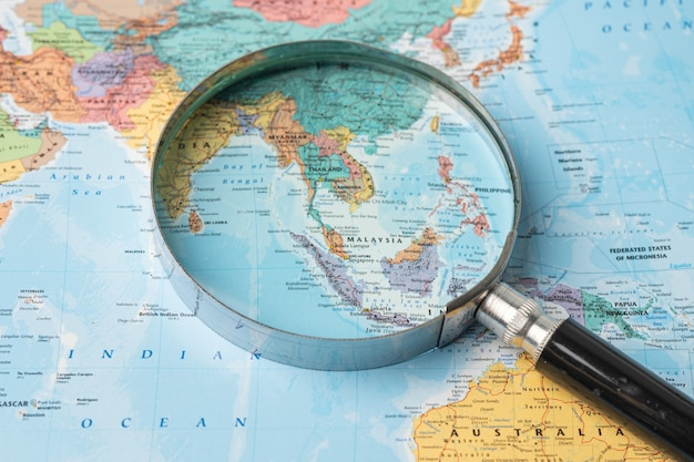 Asia, magnifying glass close up with colorful world map.