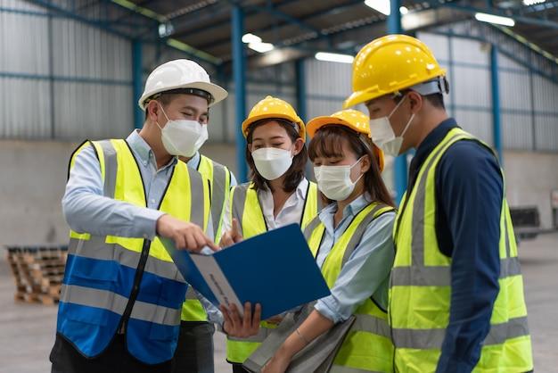 아시아 남성 및 여성 엔지니어는 창고 공장에서 팀과 논의하는 마스크와 헬멧 안전을 착용합니다.