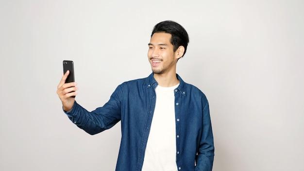 スマートフォンでアジアの男性がビデオ通話を話す