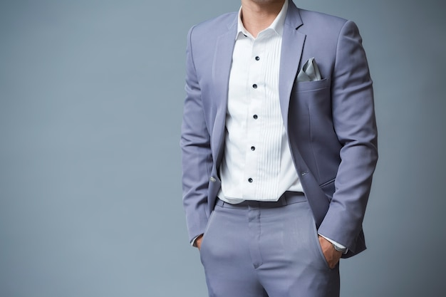 Asia man close up in suit with hands in pockets
