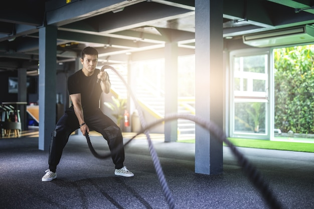 Asia man exercising with battle ropes at gym.