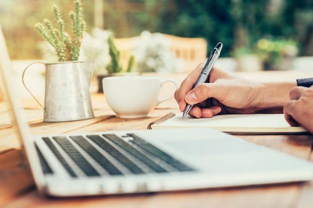 アジアの男の手は、ビンテージトーンフィルターと喫茶店の木製テーブルにノートブックペーパーを書いています。