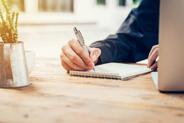 アジア人の手は、ビンテージトーンフィルターと喫茶店の木製テーブルにノートブックペーパーを書いています。