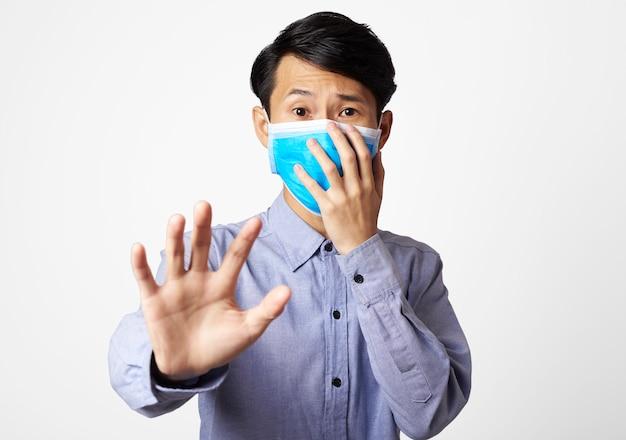 Паническое расстройство человека азии нося хирургическую маску покрывая рот и нос. защита от эпидемического вируса короны.