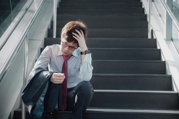 아시아 남자는 외부 계단에 앉아 작업에서 강조