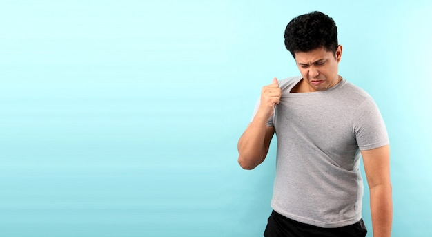 Asia man sweating excessively smelling bad isolated on blue wall.