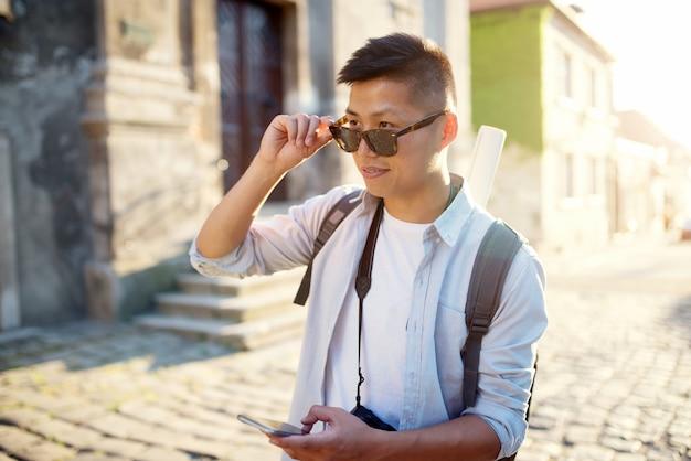 아시아 남자 걷고 화창한 여름 날 거리에서 스마트 폰을 사용 하여.