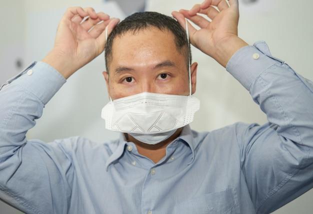 アジア人男性はパンデミックコビッド19のwhtieで分離されたn95保護コロナウイルスマスクを着用しますコピースペース付きメガネ側面図を着用します