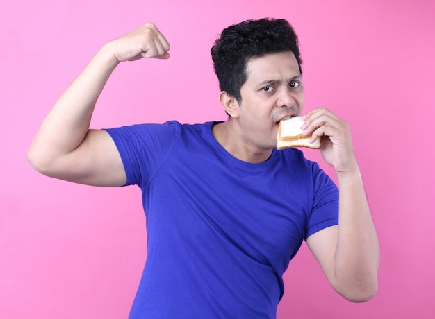 Asia men eat bread and feel strong on pink  background in studio.