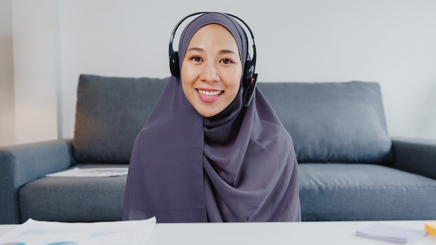 Asia muslim lady wear headphone using computer laptop talk to colleagues about plan in video call meeting while remotely work from home at living room.