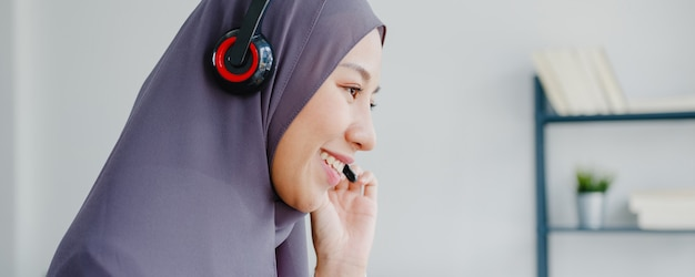 Asia muslim lady wear headphone watch webinar listen online course communicate by conference video call at house.