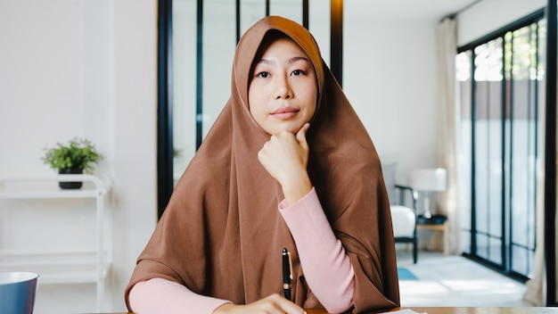 Asia muslim lady wear hijab using computer laptop talk to colleagues about plan in video call meeting while remotely work from home at living room.
