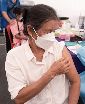 아시아 노인 여성이 야전 병원 의료진과 함께 코로나바이러스 예방접종을 하러 갔다