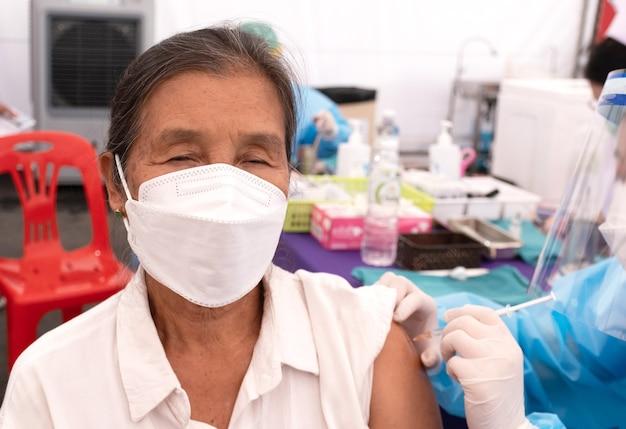 아시아 노인 여성이 현장 병원에서 의료진과 함께 코로나바이러스 covid19 예방접종을 하러 갔다