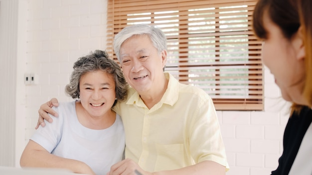 Asia smart female agent offers health insurance for elderly couples by document, tablet and laptop.