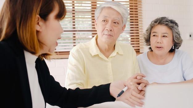 Азиатская умная женщина-агент предлагает медицинскую страховку для пожилых пар на документы, планшеты и ноутбуки.