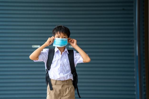 小学生の安全のため、アジアの生徒は保護マスクを着用しています。