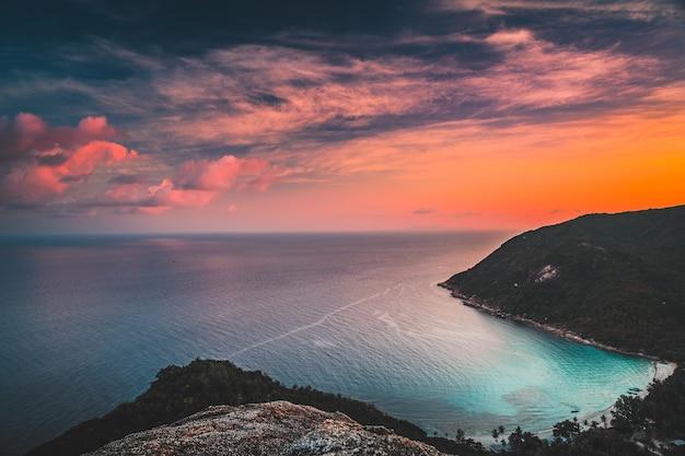 Антенна захода солнца азии: нагорье острова океана в заливе таноте, ко тао, таиланд. удивительный тайский пейзаж в теплых тонах заходящего солнца на отражении в воде. зеленые деревья на холмах, песчаный пляж в азиатской лагуне