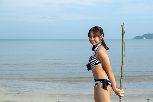コピースペースのあるビーチでビキニを着ているアジアの10代の女の子。