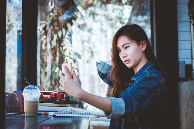 Азии подростков сидит в одиночку, используя сотовый телефон с selfie в кафе.