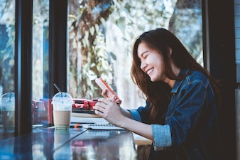 Asia teenage sitting alone using cellphone with smiling in cafe.