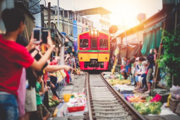 아시아 관광객이 기차를 타고 사진을 찍고 휴가에 놀랍도록 신선한 시장을 통과합니다.