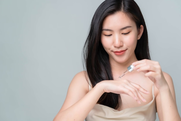 회색 배경에 완벽한 화장을 한 피펫으로 얼굴에 히알루론산 혈청을 바르는 아시아 여성. 뷰티 컨셉