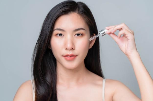 피펫으로 얼굴에 히알루론산 혈청을 바르는 아시아 여성