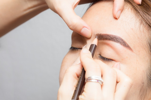 Asia woman applying permanent make up on eyebrows tattoo