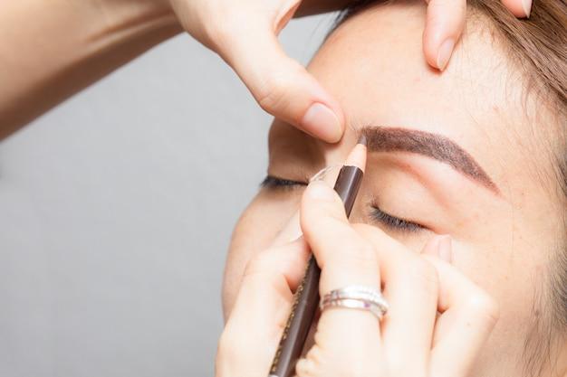 永久に適用するアジアの女性は眉毛の入れ墨にメイクアップ