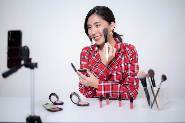 Азиатский женский бьюти-блогер делает макияж и рассматривает бьюти-продукты для видеоблога