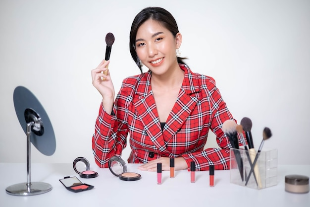 Asia woman beauty blogger does make up, reviews beauty product for video blog,