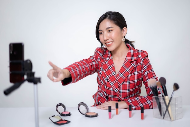 Asia woman beauty blogger does make up, reviews beauty product for video blog